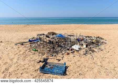 A Large Pile Of Rubbish On The Wide Sandy Shore Of The Black Sea.