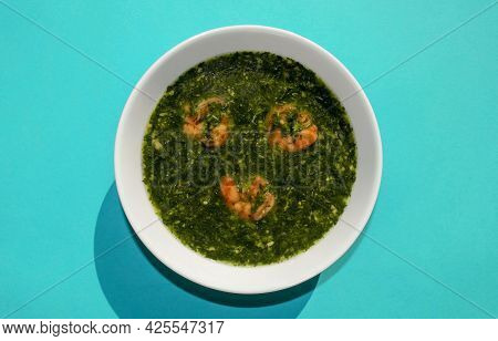 Famous Traditional Arabic Cuisine. Molokhia Green Soup With Shrimps On Blue Background. Flat Lay, To