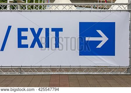 Blue Exit Sign And Direction Arrow At Temporary Wall