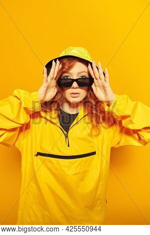 Youth style. Modern hip-hop dancer. Stylish girl in yellow hoodie and sunglasses poses at studio on a yellow background.