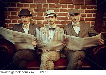 Retro style. Three handsome men in elegant suits sit on a leather sofa and read newspapers. Newspaper editorial office. Men's fashion. Men's club.