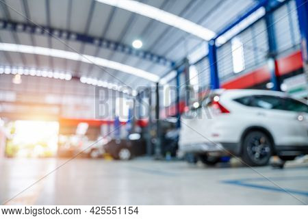 Blurred Of Car Repair Station Paved With Epoxy Floor And Electric Lift For A Car That Comes To Chang
