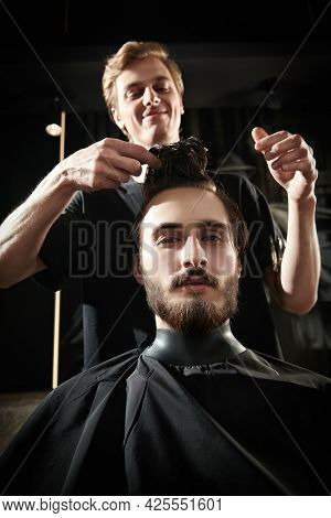 Handsome hairdresser cutting hair of male client. Hairstylist serving client at barbershop.