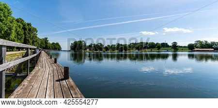 An Idyllic Lake With A Wooden Boardwalk Along The Side And Sailboats Moored In The Background