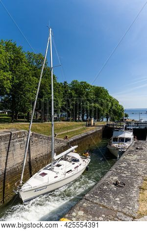 Berg, Sweden - 21 June, 2021: Boats Travelling Upriver In The Locks And Sluices Of The Gota Canal