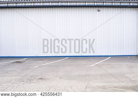 White Corrugated Iron Sheet Used As A Facade Of A Warehouse Or Factory. Texture Of A Seamless Corrug