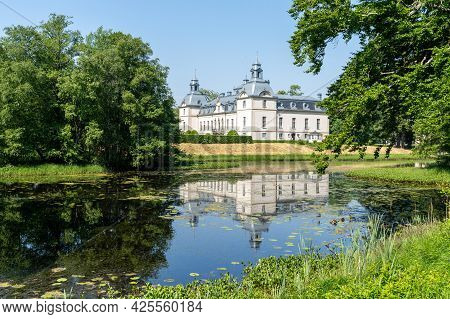 Tomelilla, Sweden - 19 June, 2021: Picturesque Kronovall Castle And Gardens Reflected In A Pond In T