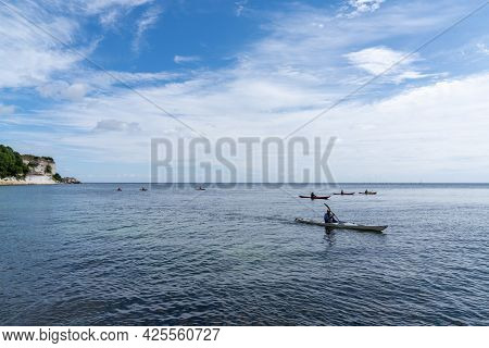 Hojerup, Denmark - 12 June, 2021: Group Of Sea Kayakers Paddling Off The Coast Of Denmark At Stenvs