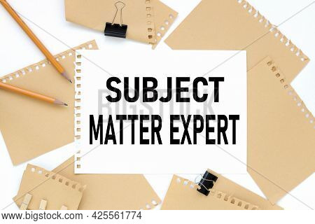 Subject Matter Expert. Text On White Notepad Paper. On A White Photo With Torn Paper