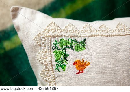 Embroidery Element With Chicken On The Pillow, Close-up. Colorful Embroidery Design On White Linen P