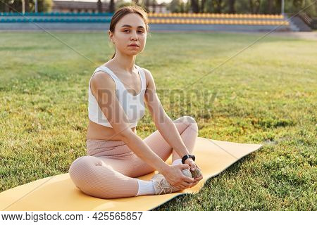 Peaceful Sporty Woman Sitting On Karemat In The Lotus Pose In Stadium, Wearing White Top And Beige L