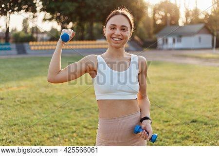 Outdoor Shot Of Young Female Athlete With Dumbbells Stretching And Warming Up In Stadium, Looking Sm