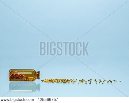 A Product Of Beekeeping In Medicine. Flower Pollen Pellets Scattered Near The Overturned Glass Jar.
