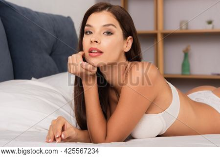 Passionate Woman Looking At Camera While Lying On Bed