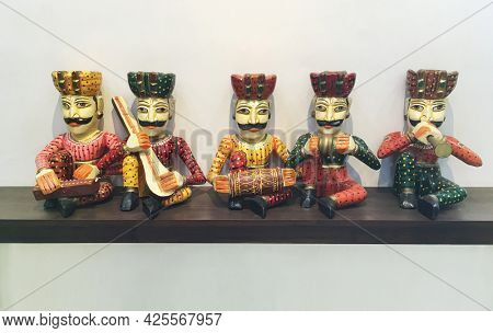 Group of wooden handcrafted dolls from Rajasthan artist. Miniature Indian traditional figures or folk art from India.