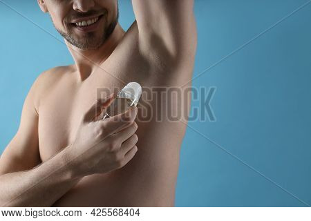 Man Applying Deodorant On Turquoise Background, Closeup. Space For Text