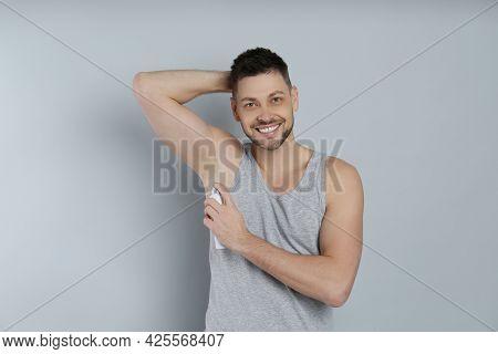 Handsome Man Applying Deodorant On Grey Background