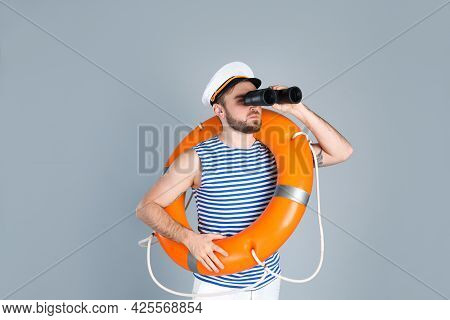 Sailor With Binoculars And Ring Buoy On Light Grey Background