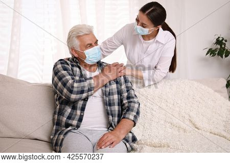 Doctor Taking Care Of Senior Man With Protective Mask At Nursing Home