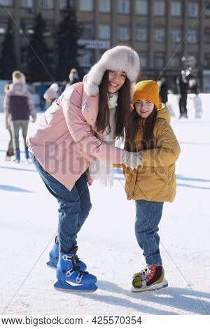 Mother And Daughter Spending Time Together At Outdoor Ice Skating Rink