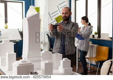 Design Constructor Looking At Smartphone For Project Of Architectural Structure. Engineer Standing A