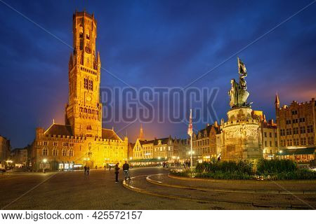 Belfry tower famous tourist destination and Grote markt square with Jan Breydel and Pieter de Coninck Monument in Bruges, Belgium on dusk in twilight