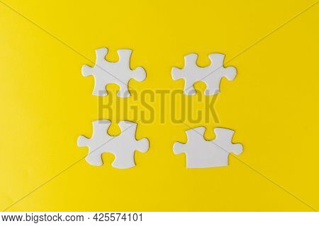 Pieces Of White Jigsaw Puzzle On Yellow Background