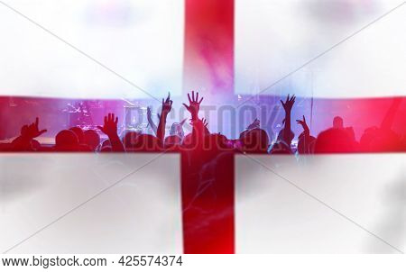 Football fans supporting England - crowd celebrating in stadium with raised hands against England flag