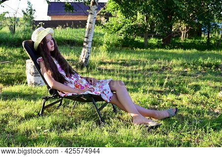 Pretty Girl With Long Wavy Hair In Hat Is Sitting On Chaise Longue Against  Background Of Rural Land