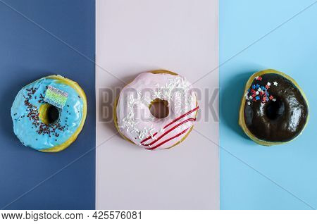Donuts With Icing On A Colored Background. Sweet Donuts On A Three-color Background Close-up