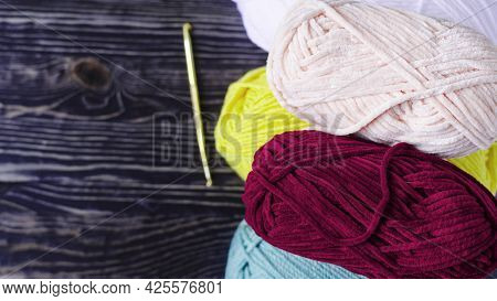 Balls Of Colored Yarn And A Knitting Hook On The Background Of A Dark Copy Space Tree. The Concept O