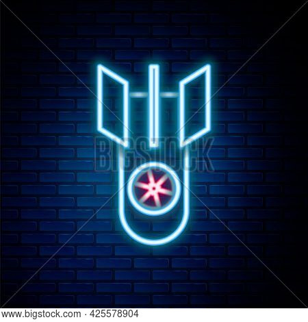 Glowing Neon Line Nuclear Bomb Icon Isolated On Brick Wall Background. Rocket Bomb Flies Down. Color
