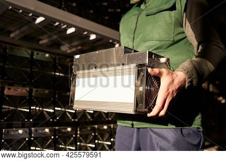Mover Holding Bitcoin Asic Miner In Warehouse. Worker With Asic Mining Equipment On Stand Racks For