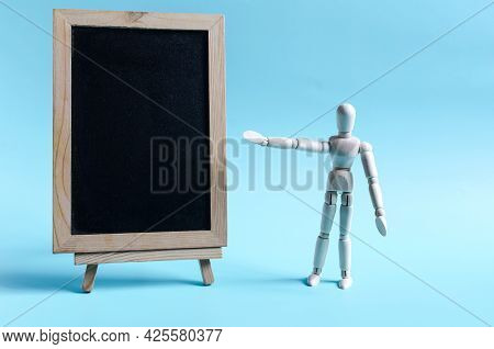 The Figure Of A Wooden Man Pointing To A Clean Slate. Figure Of A Wooden Man On A Light Background O