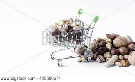 A Cart Full Of Different Nuts, And A Mountain Of Nuts On A White Background Of Different Nuts. Assor
