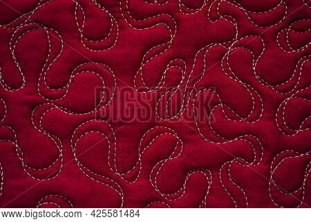 Close Up Texture Of Quilting By Free-motion Machine Technique. On Dark Red Clothes Background