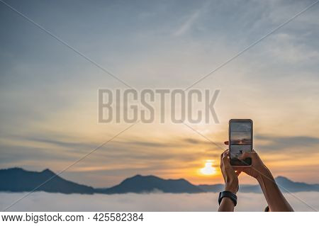 Tourist Hand Use Mobile Phone Take A Photo Of Sunrise And Sea Of Fog On Phu Thok  At Chiang Khan In