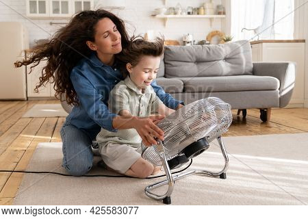 Cheerful Young Mom Or Nanny Have Fun With Preschool Boy At Home Sitting Together In Front Of Big Fan