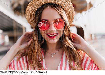 Portrait Of Sensual Blonde Woman Wears Trendy Pink Summer Glasses. Outdoor Photo Of Good-humoured Li
