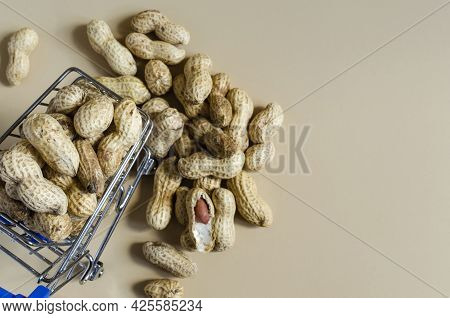 Peanuts In A Metal Basket And Scattered Peanuts In A Shell On A Light Brown Background Of Kopi Space