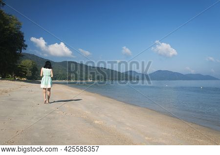 A Lone Female Walking On Long Beach At Batu Ferringhi On Sunny Morning In Penang Malaysia.