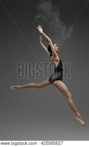 Leaping Woman With Raised Arms Against Gray Background