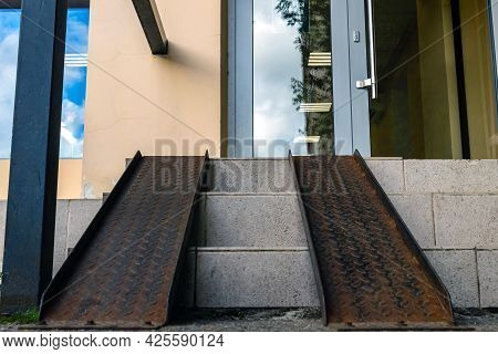 Metal Ramp For Low-mobility Citizens. On Top Of The Steps Of The Store.
