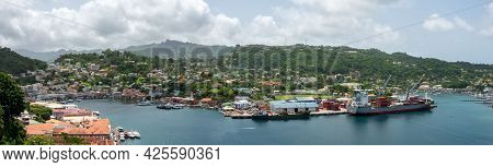 St Georges, Grenada - June 17, 2021: A Panorama Of St Georges, Grenada And A Cargo Ship In The Bay.