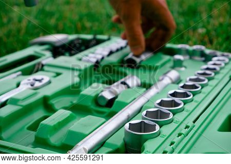 Close-up Photo Of A Set Of Sockets With A Screwdriver And A Ratchet In A Green Plastic Case Against