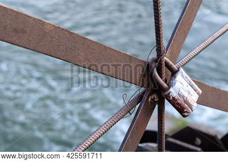 An Old Iron Lock Hangs On A Rusty Railing. Castle On The Old Bridge. Rusty Castle On A Background Of