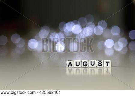 August Text On White Cubic Blocks. The Letters Are Written On The Cubes In Black Letters Highlighted