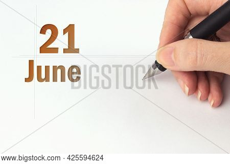 June 21st . Day 21 Of Month, Calendar Date. The Hand Holds A Black Pen And Writes The Calendar Date.