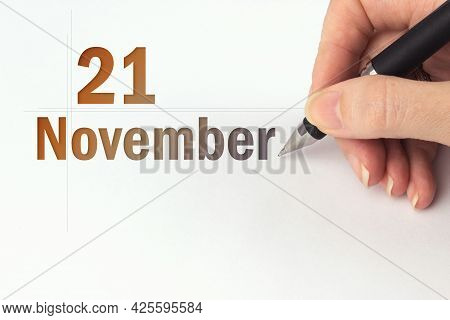 November 21st . Day 21 Of Month, Calendar Date. The Hand Holds A Black Pen And Writes The Calendar D