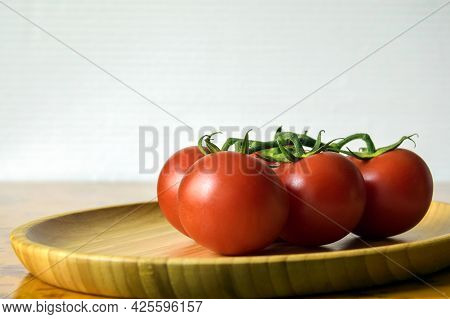 Ripe Fresh Tomato In Wooden Plate On Kitchen Table. Tasty Red Heirloom Tomatoes. Vegetarian Food, Ra